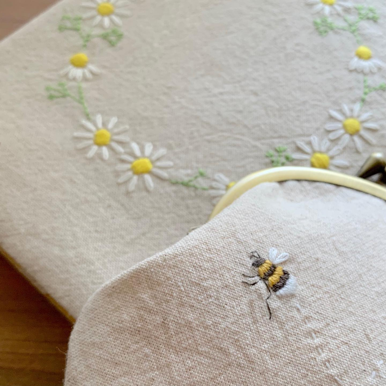 #カモミール刺繍 の#がまぐちポーチ と#単行本サイズ のブックカバーminneにて本日より再販スタートしました。プロフィールからminne に飛べます🕊#花言葉#逆境で生まれる力#逆境に耐える#蜂#ハチ##bee #honeybee #カモミール刺繍 #花刺繍 #刺繍 #embroidery #手刺繍#handembroidery #handmade #手仕事#手作り#針仕事#needlework#カモミール#カミツレ#chamomile #はなのある暮らし #tomoprix#minne